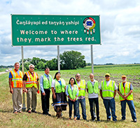 This new Dakota-English language sign welcomes travelers to the Lower Sioux Indian Community in District 8. The sign reads 'Welcome to where they mark the trees red.'