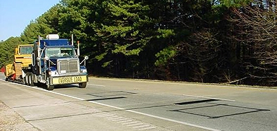 "A truck with an ""Oversize Load"" sign approaches a weigh-in-motion site"