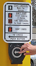 Hand pressing crosswalk button